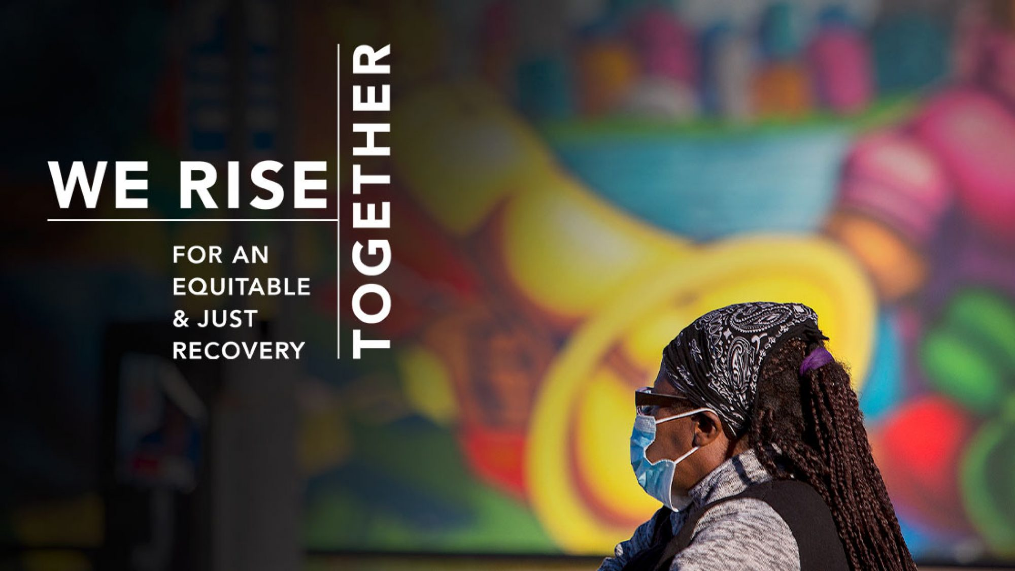 Black woman, masked, in front of a colorful mural. Overlay text says We rise together for an equitable and just recovery.