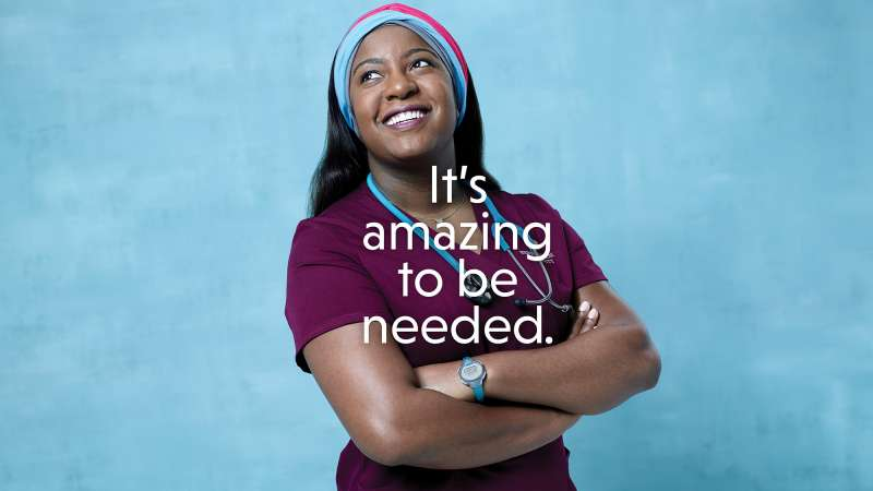 Text: It's amazing to be needed. A black woman in nurse's scrubs and a colorful head scarf.