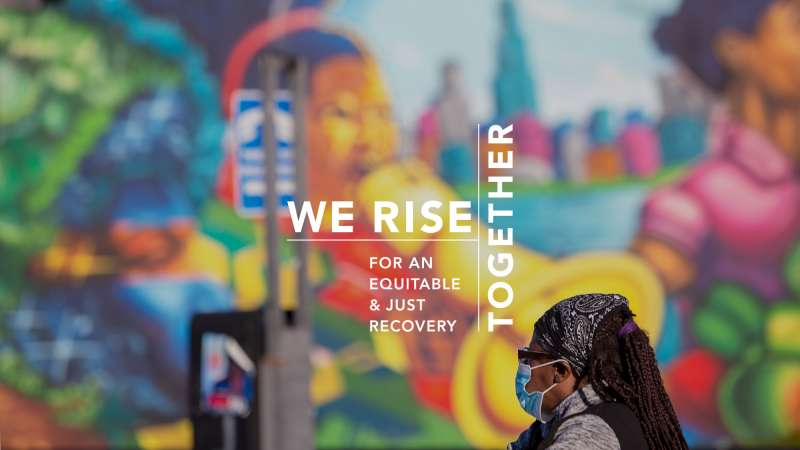 Image text: We Rise Together. A Black woman in a face mask contemplates a mural in Chicago.
