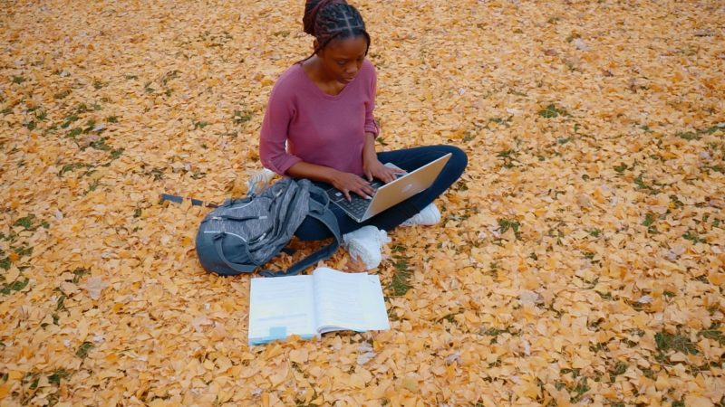A young Black woman studying outdoors, on a leaf-covered lawn with a laptop computer balanced on her legs.
