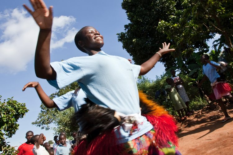 Action shot: young black people in blue shirts and colorful pants dancing.